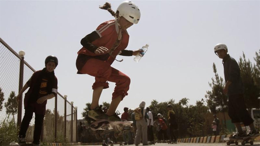 An Afghan girl jumps on her skateboard in Kabul on June 21, 2012; hundreds of Afghan boys and girls celebrated World Skateboarding Day in the national capital [File: Ahmad Jamshid/AP]