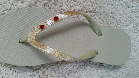 brown and gold flip flops with baseball charm embellishments
