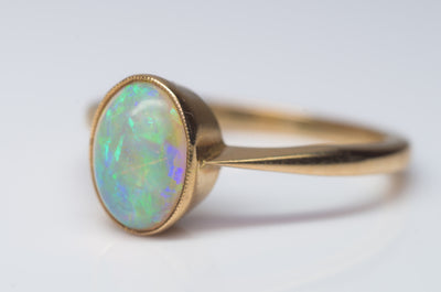 18K YELLOW GOLD AND BEZEL SET OPAL SOLITAIRE RING