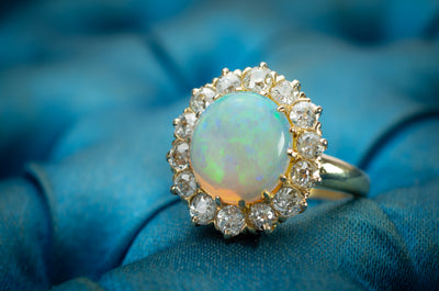 ANTIQUE ROUND OPAL AND DIAMOND HALO RING