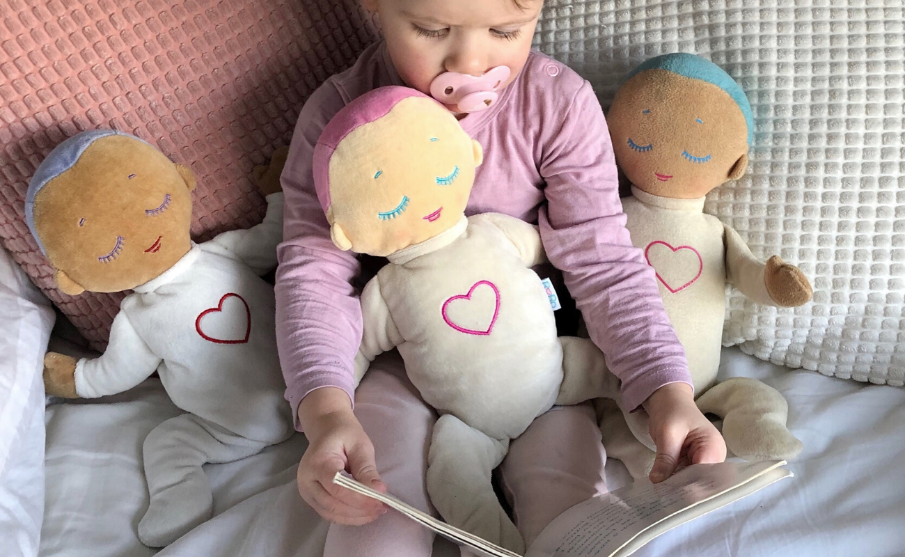 Girl reading with Lulla dolls