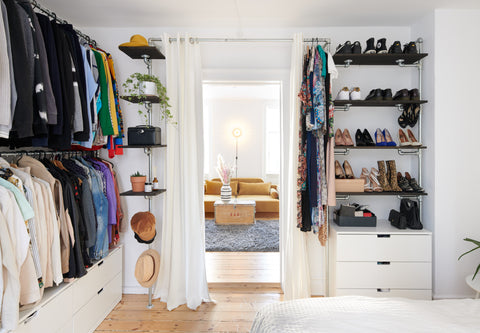Open wardrobe solution by RackBuddy with hanging clothes and shelves. All sorted in groups of colours.