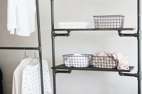 Shelves in dark pine being hold by a cloths rack made of black water pipes. Some simple and clean accessories and clothes are stored on it.