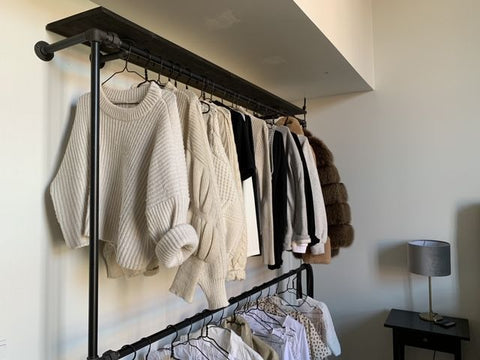 Hanging cloths from a wall mounted rack out of water pipes in black. A shelf on top in dark pine.