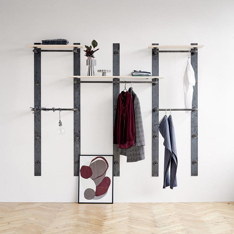 Super flexible package solution for a modular wardrobe system consisting of rustic wooden shelves with built-in clothes rails and a separate clothes rail in industrial iron pipes
