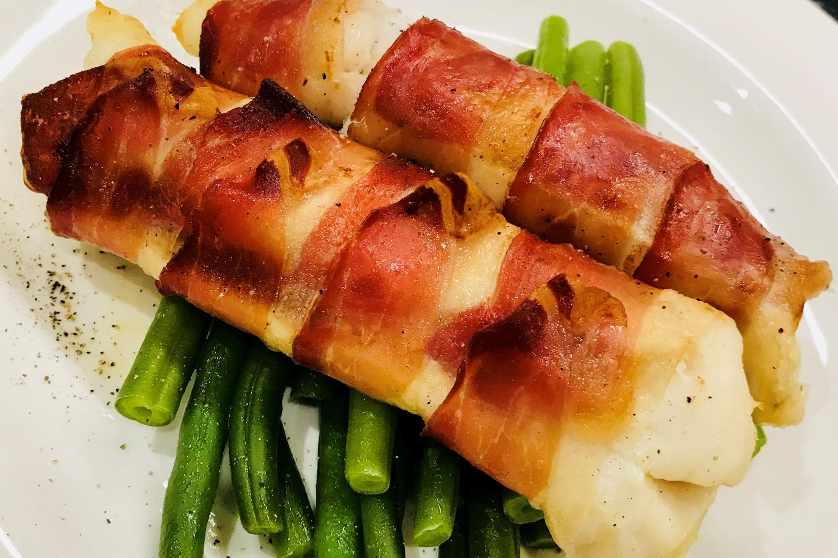 Cod fillets wrapped in Black Combe Ham with buttered greens