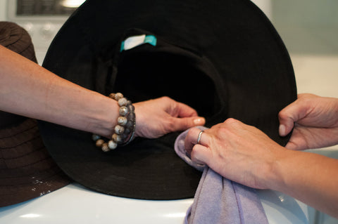 Spot clean the dirty inside of hat brims with Roux Maison Delicate Detergent and a microfiber cloth for best results.