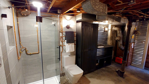 masculine interior design of a bathroom showing exposed piping in an industrial style bathroom having a wall-mount copper shower integrated.