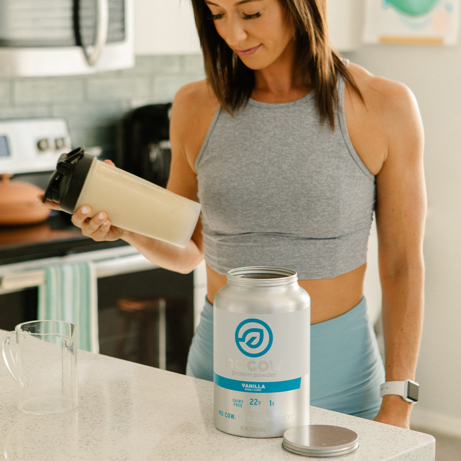 Woman holding No Cow Vanilla Protein Powder