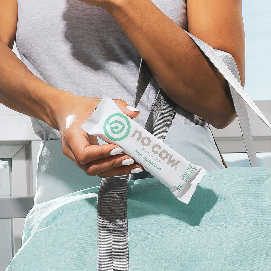 Woman holding No Cow Mint Cacao Chip Protein Bar