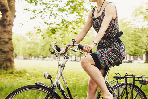 woman riding bicycle in grassy area
