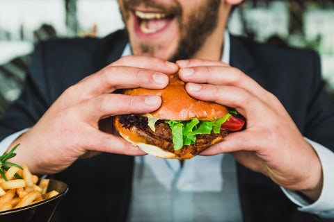 man holding a burger with vegetables and meat