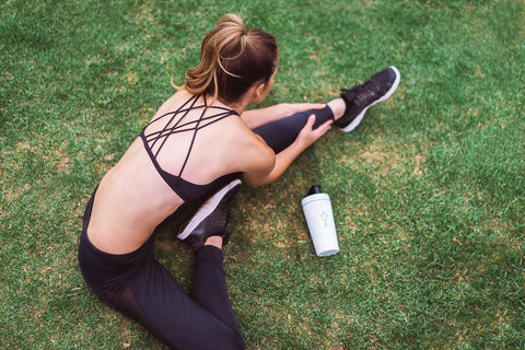 woman doing hamstring stretch on a grassy field