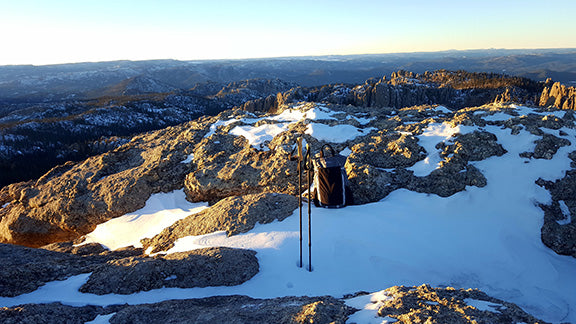 Hiking poles in the snow on top of a mountain