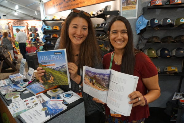 two women stand with the long trails book at a signing