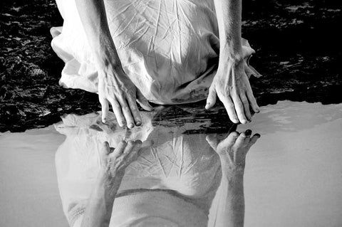 Woman kneels by water reaching hands to touch the surface of the water and her reflection— She Meeta Herself © Lisa Seed