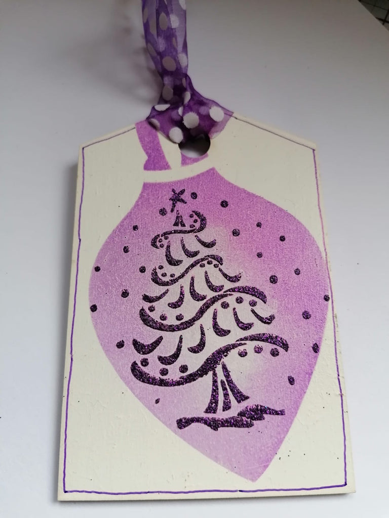 Glitter paste applied using stencil on to MDF Christmas tag