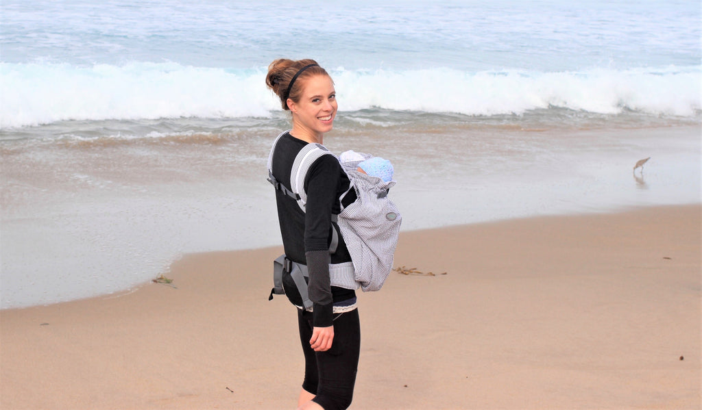 Woman carrying twins in Weego TWIN baby carrier on the beach