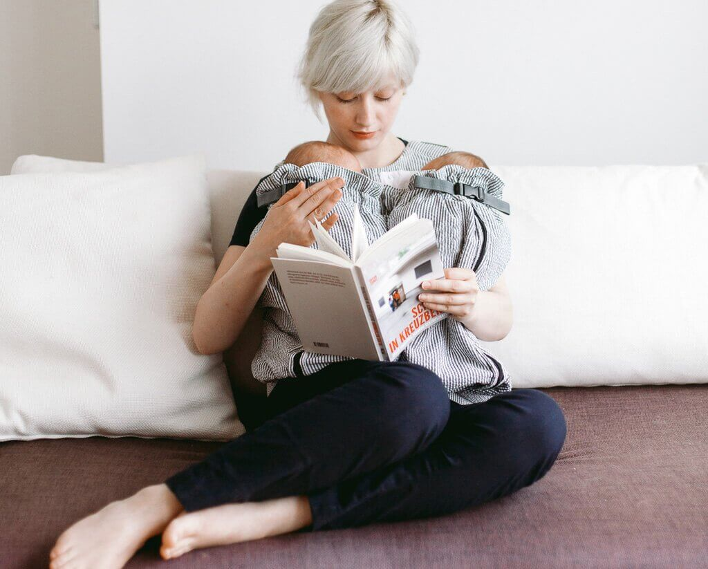 Young mom reading a book with twins in Weego TWIN carrier