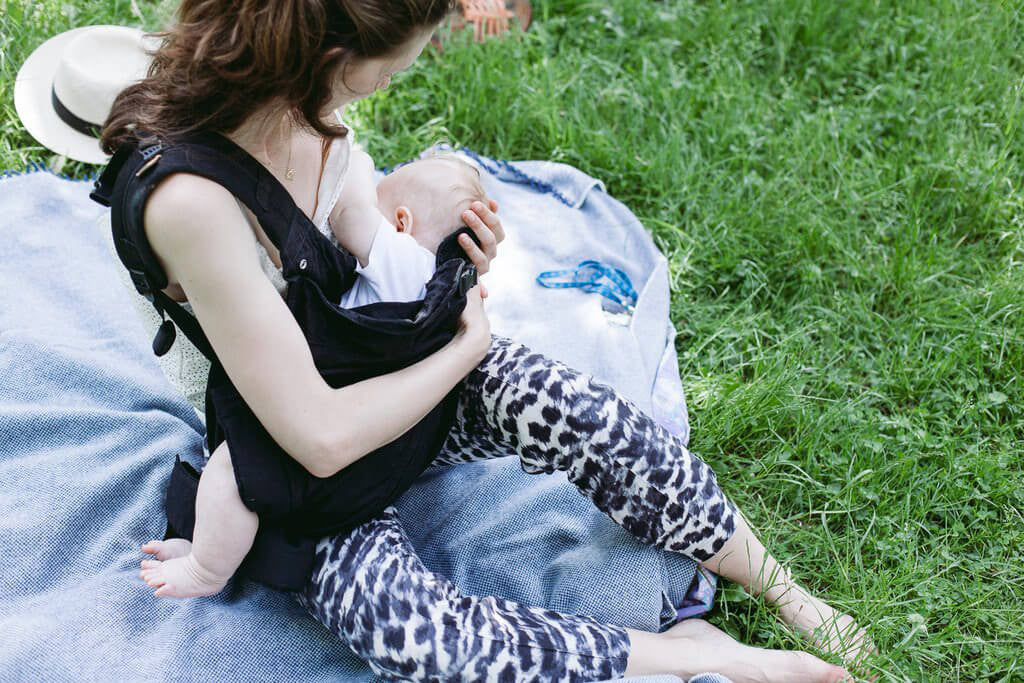 Woman nursing baby in Weego ORIGINAL baby carrier