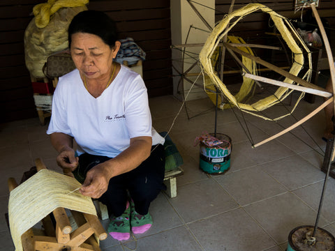An artisan woman uses a handmade spinning wheel to spool the thread onto a bobbin.
