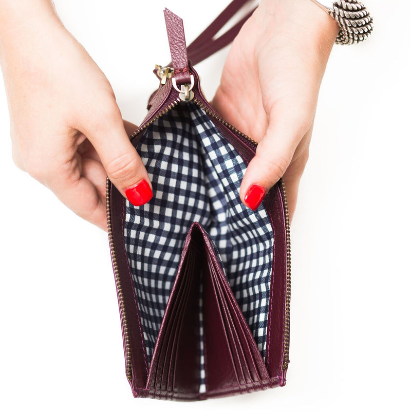 Interior of Forten wristlet in biking red oil raw leather has a hidden wallet for 8 cards and contrasting cotton lining.