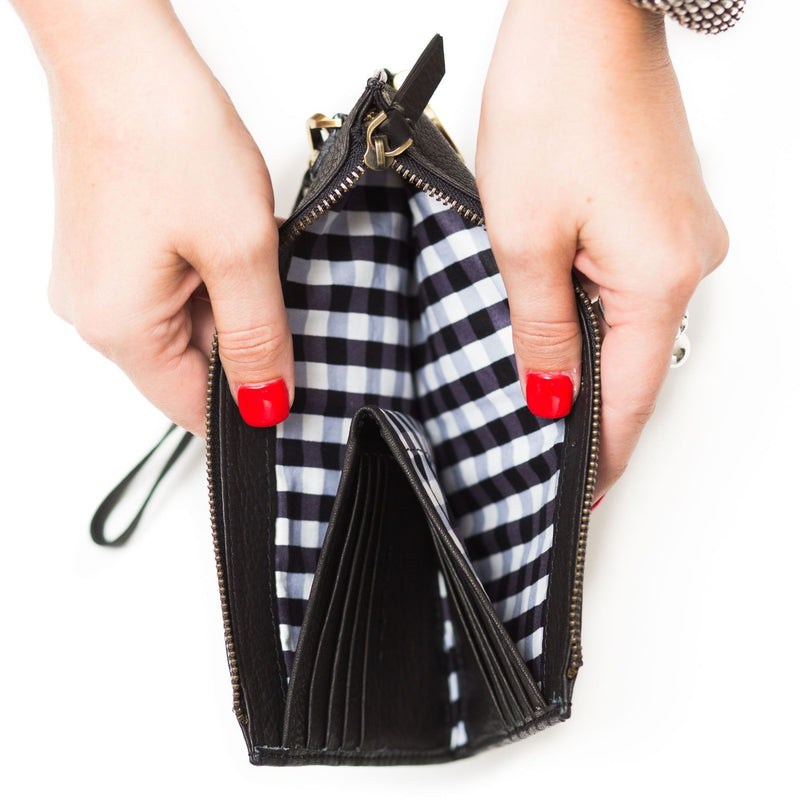 Interior of Forten wristlet in black raw leather has a hidden wallet for 8 cards and contrasting cotton lining.