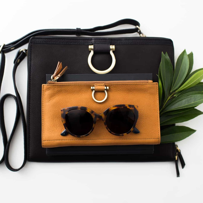 The M crossbody handbag in black raw leather will easily fit your wallet and sunglasses.