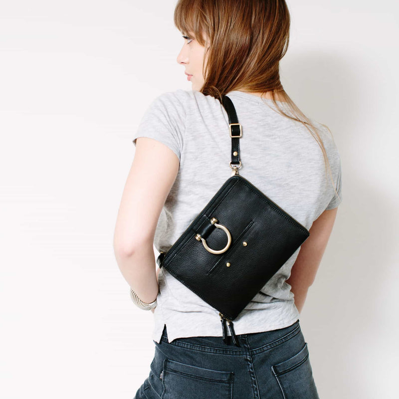 Wear the M mini crossbody bag in black raw leather over your shoulder to show off the Omega brass hardware.