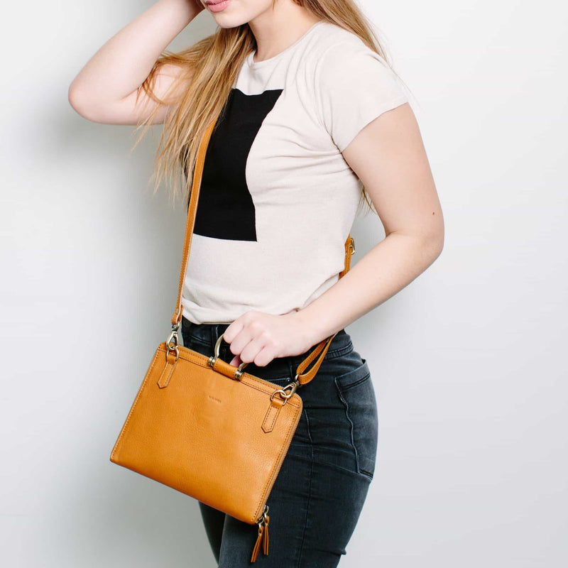 Wear the M mini crossbody bag in whisky tan raw leather across the body to carry your essentials.
