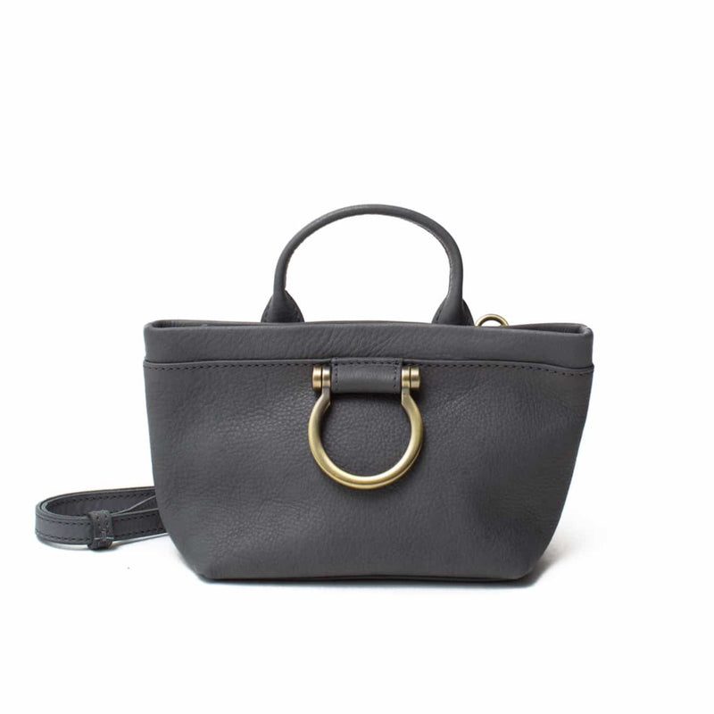The Roger mini crossbody in gray raw leather features a top handle and Omega plated brass hardware.