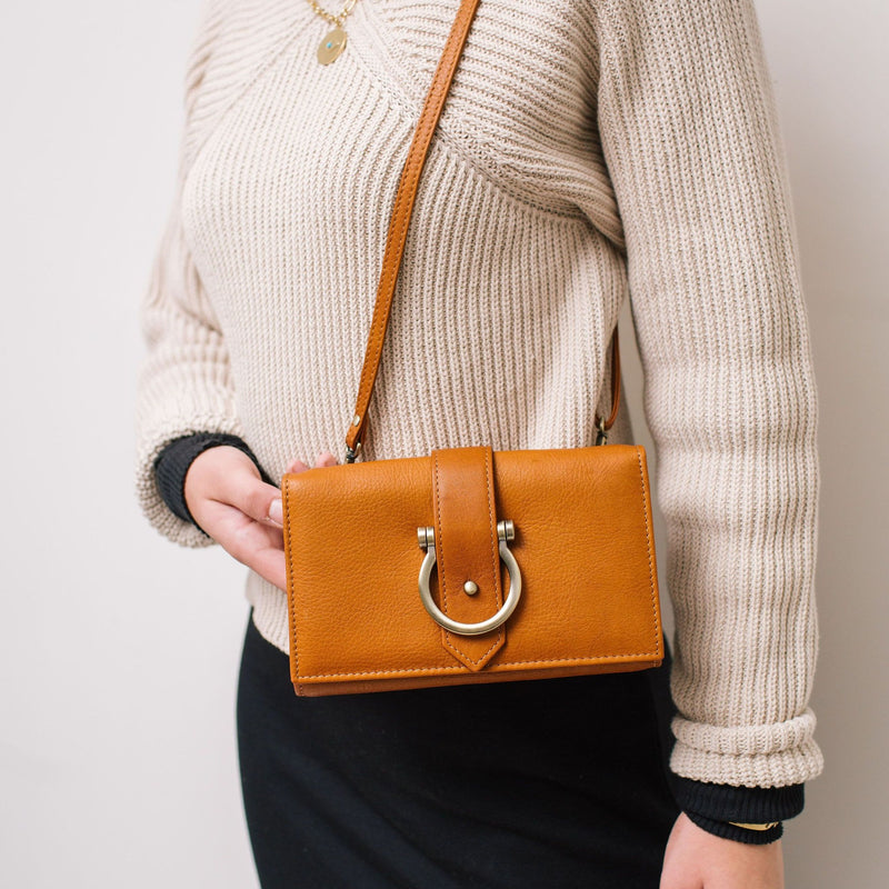 Staney in whisky tan raw leather features an adjustable strap so you can wear it over the shoulder.