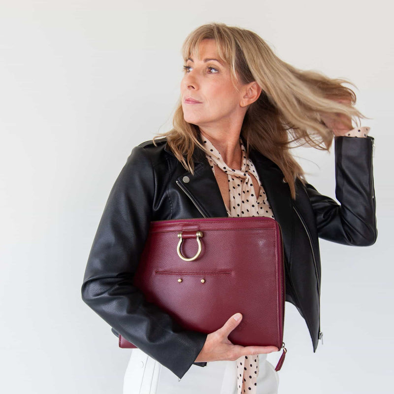 Carry the M large crossbody bag in deep red oil leather like a clutch.