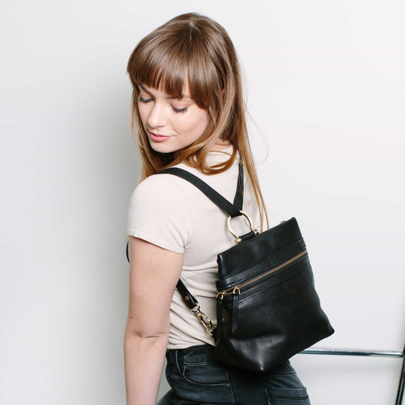 Wear the Pepper convertible crossbody bag in black raw leather as a backpack.