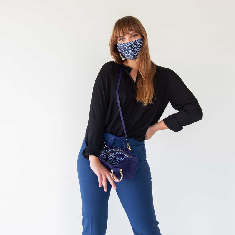 Wear the Roger mini crossbody in indigo raw leather over the shoulder.