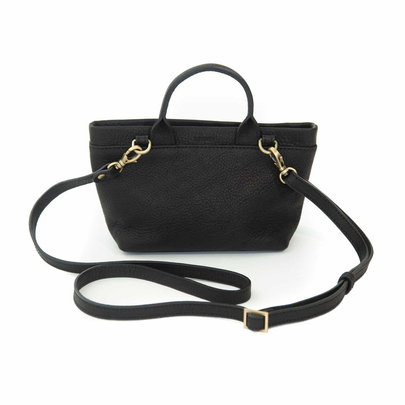 The Roger mini crossbody bag in black raw leather has an adjustable and removable strap.