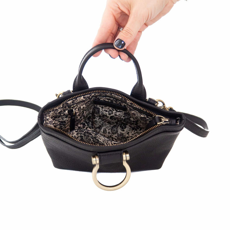 The Roger mini crossbody bag in black raw leather has two interior pockets.