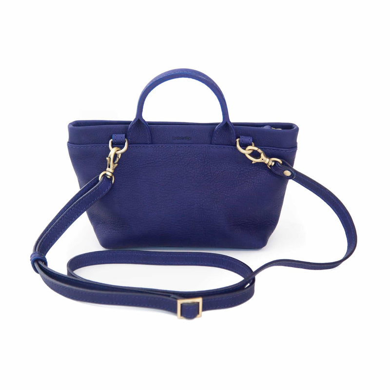 The Roger mini crossbody bag in indigo raw leather has an adjustable and removable strap.