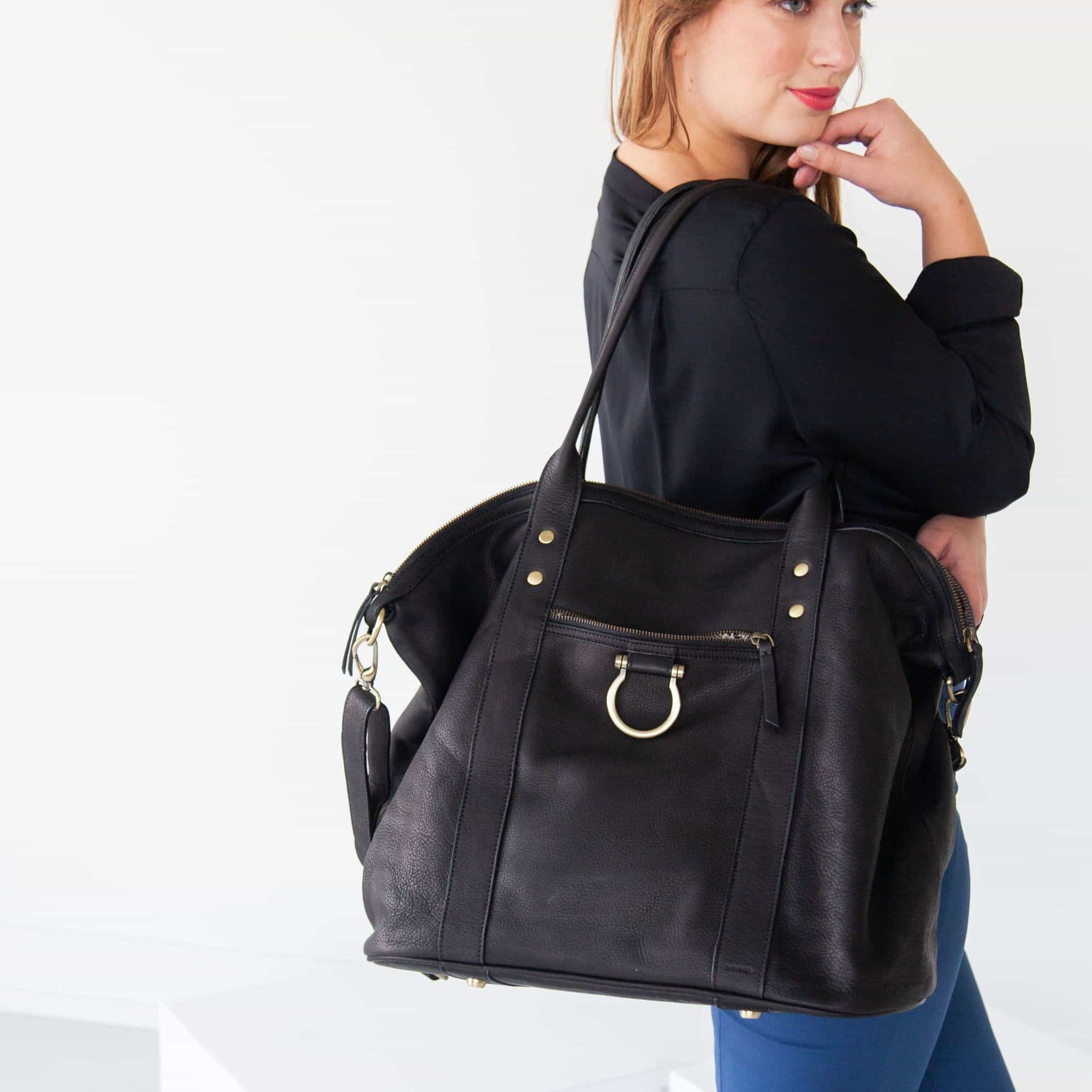 Wear the So Honey weekender in black raw leather over your shoulders by the top handles.