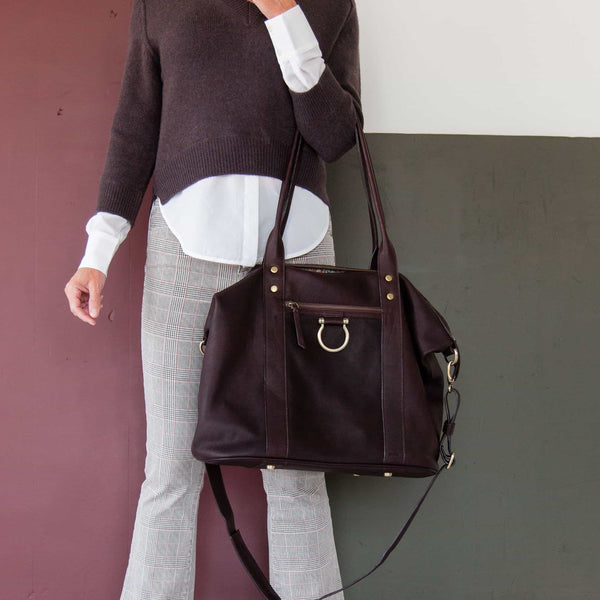 Hold the So Honey weekender tote in chocolate brown raw leather by the top handles.