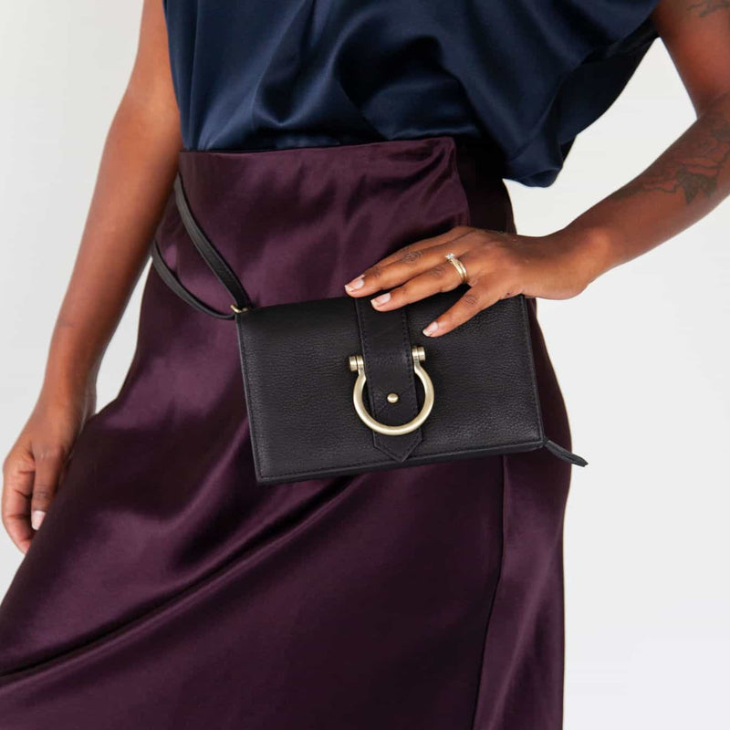 Wear the Staney crossbody wristlet wallet in black raw leather as a belt bag.