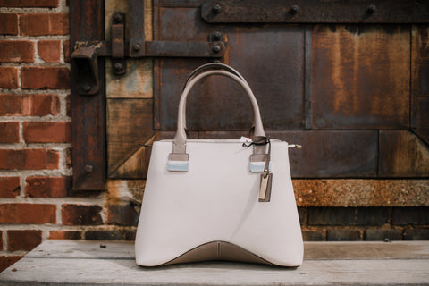 Stella Collection white handbag displayed outside a brick wall with a wood barn door.