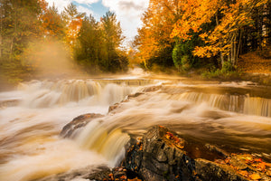 Sunrise at Bond Falls in Autumn with the steam rolling off the river.