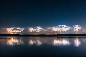 Thunderstorm in the distance over Tainter Lake with stars overhead near Menomonie, Wisconsin.