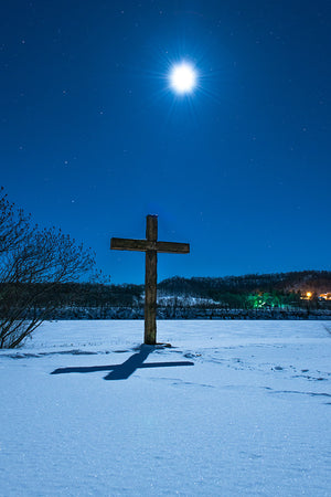 Full moon over a cross in the winter near Durand, Wisconsin.