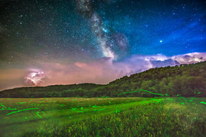 Fire flies in a field with the Milky Way Galaxy and lightning from a thunderstorm in the sky near Elmwood, Wisconsin.