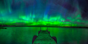 A dock and the northern lights dancing over a lake in Wisconsin.