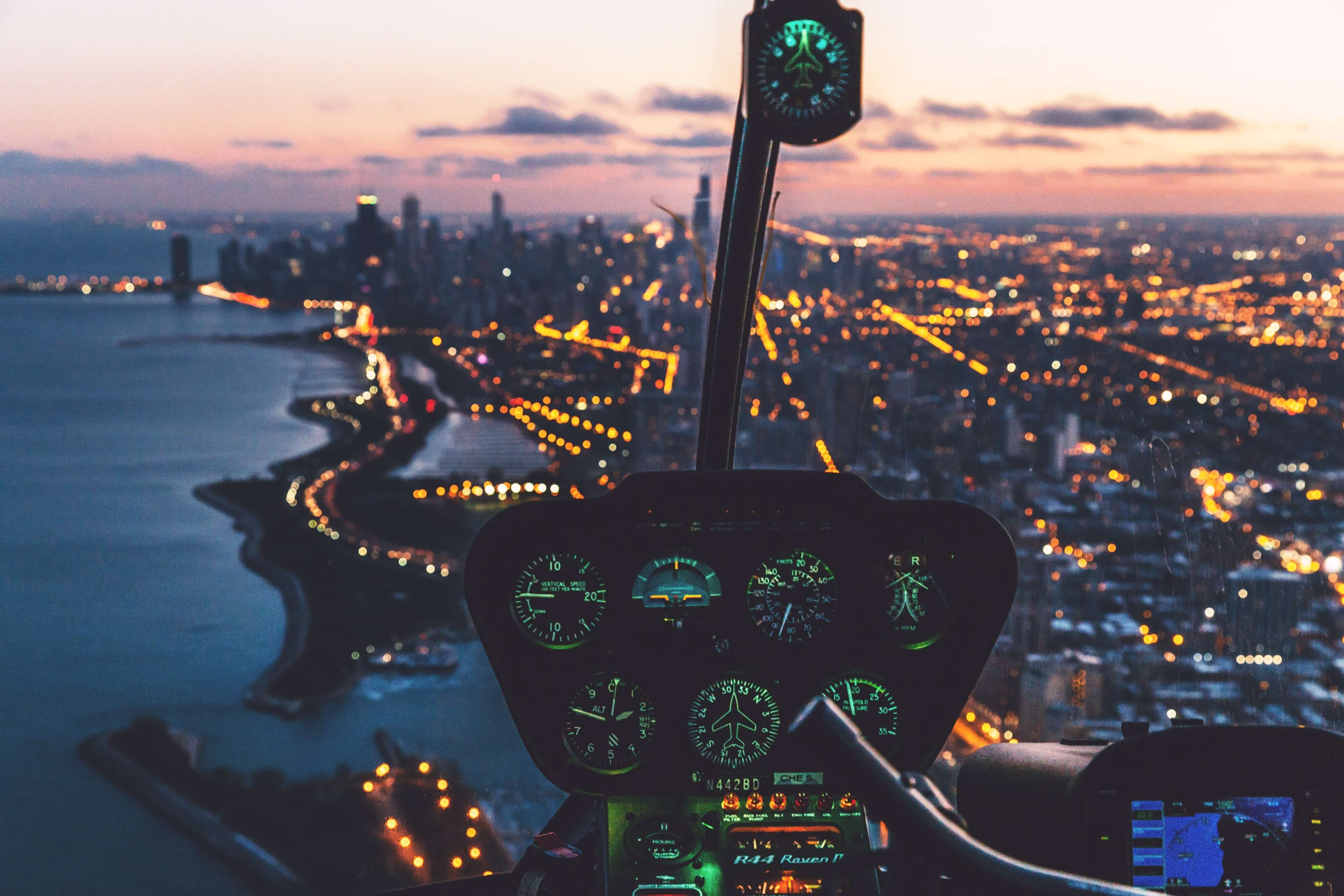 view from helicopter cockpit over city lights