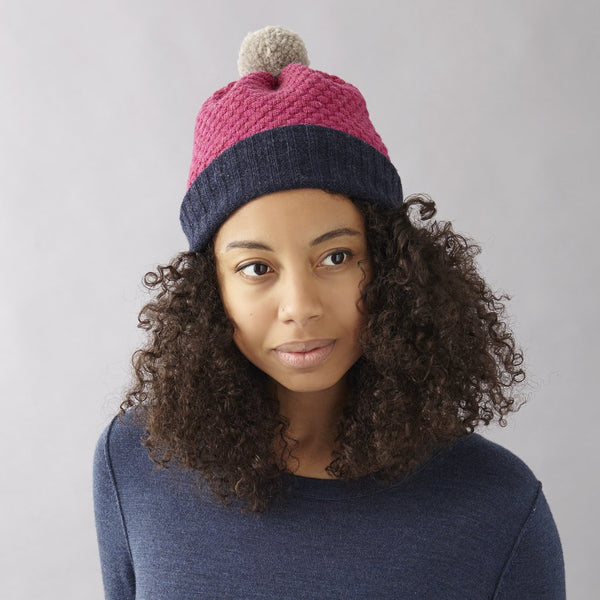 A plumb coloured knitted bobble hat with a navy cuff and cream coloured bobble.  Made in England by Catherine Tough from 100% soft merino wool.