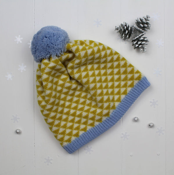 A knitted pom pom hat by Miss Knit Nat.  A funky geometric triangle pattern in piccalilli and sky blue colours. Made and designed in Britain